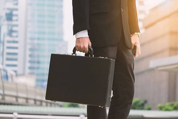 low-section-of-a-businessman-in-black-suit-and-trousers-carrying-black-briefcase-while-standing_t20_pxe3mj